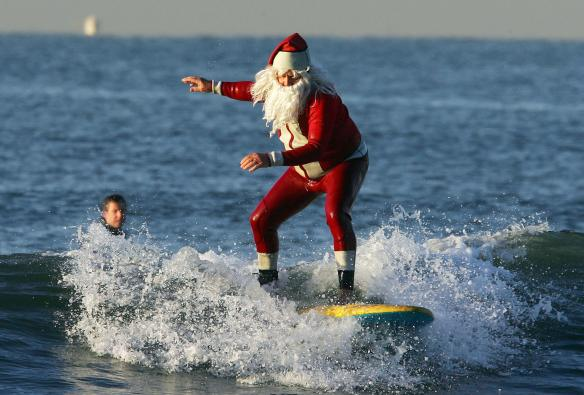 Seal Beach, UNITED STATES:  Michael Pless, dressed in a Santa wetsuit and beard enjoys a Christmas eve surf at Seal Beach, California, early 24 December 2006.  Warm temperatures are forcast for Christmas in southern California.  Pless, a surfing instructor, also has a tuxedo wetsuit for New Years eve.  AFP PHOTO / Robyn BECK  (Photo credit should read ROBYN BECK/AFP/Getty Images)